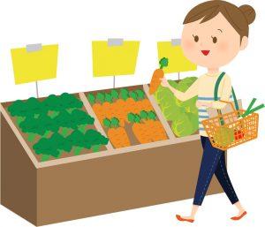 スーパーの売り場で野菜を選ぶ主婦